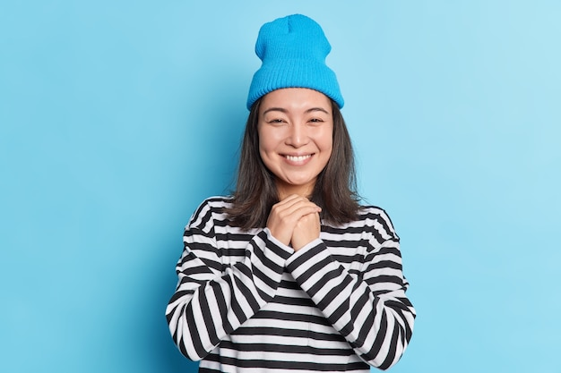 Vrij aziatisch meisje houdt handen bij elkaar kijkt met zachte glimlach op camera heeft tevreden gezichtsuitdrukking hoort iets aangenaams