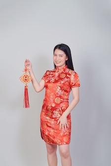 Vrij aziatisch meisje met chinese traditionele kledingcheongsam of qipao die voetzoeker houdt. chinees nieuw jaarconcept, vrouwelijk model dat in grijze studioachtergrond wordt geïsoleerd