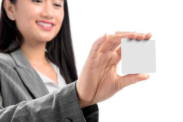 Vrij aziatische bedrijfsvrouw die leeg adreskaartje bij haar hand status toont