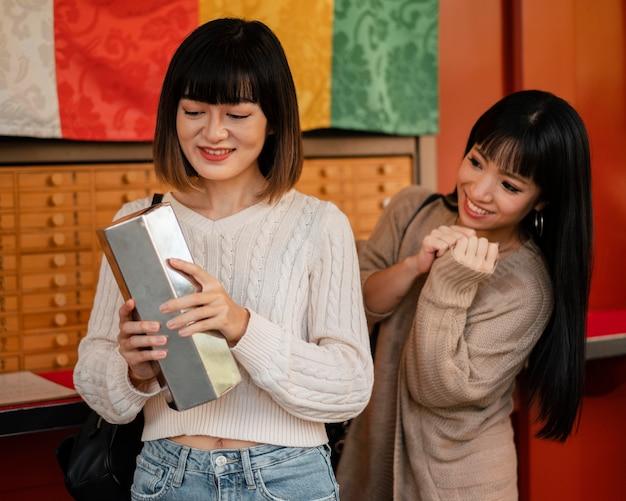 Vrij aziatische meisjes die samen een product controleren