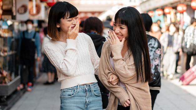 Vrij aziatische meisjes die samen lachen