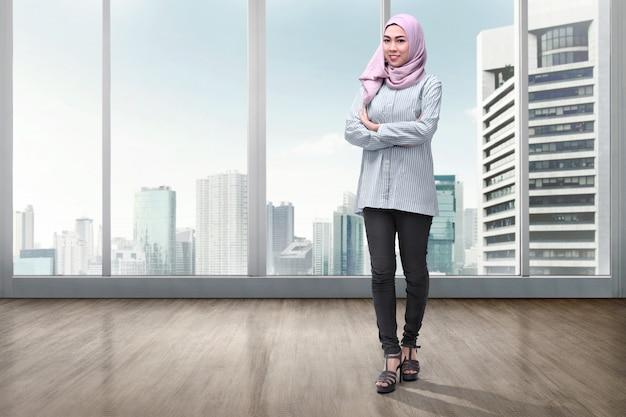 Vrij aziatische moslimvrouw in sluier met gekruiste wapens