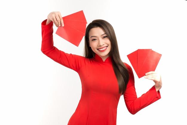 Vrij aziatische vrouw die rode ao dai draagt en rode envelop voor maannieuwjaar houdt.