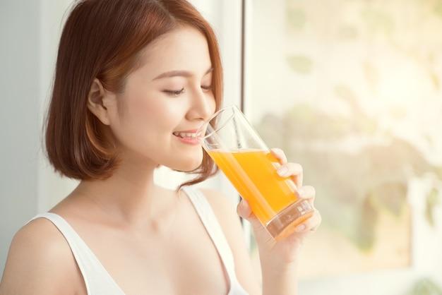 Vrij aziatische vrouw die sap thuis in de woonkamer drinkt