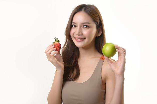 Vrij aziatische vrouw met appel en aardbei