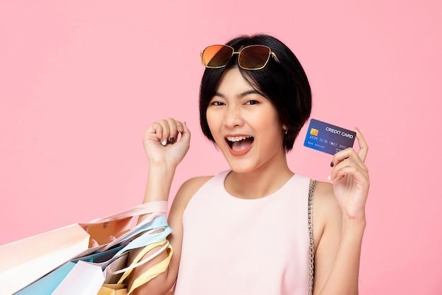 Vrij aziatische vrouw met het winkelen zakken die creditcard tonen