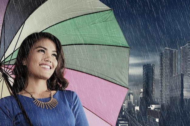 Vrij aziatische vrouw met paraplu bij regen