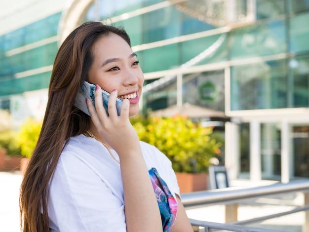 Vrij aziatische vrouw praten over de telefoon glimlachen