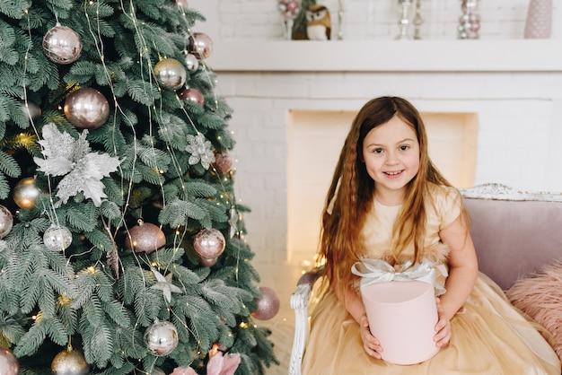 Vrij blank schoolmeisje zitten in de buurt van versierde kerstboom met haar kerstcadeau