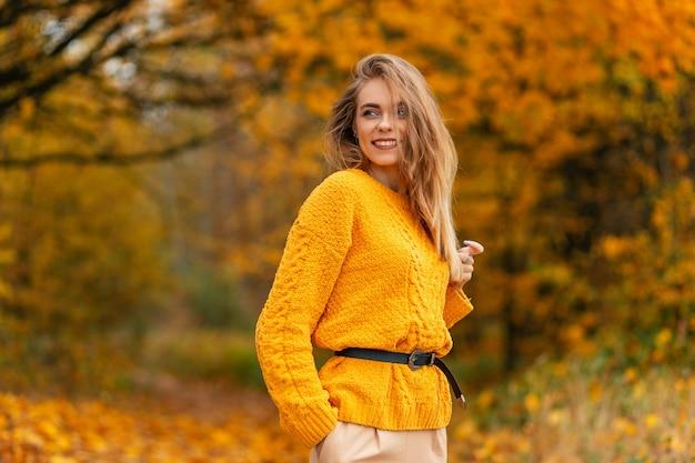 Vrij blanke gelukkige vrouw met zoete glimlach in vintage gebreide trui rust en geniet in het park met herfstgeel gebladerte. vrouwelijke gekleurde stijl en herfstschoonheid