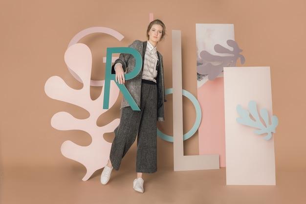Vrij blanke jonge vrouw poseren voor de letterlijke en kubieke installatie
