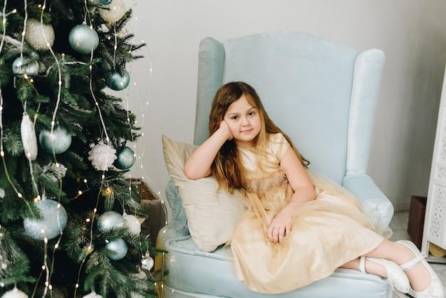Vrij blanke schoolmeisje zit in een fauteuil in de buurt van versierde kerstboom