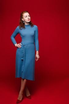 Vrij blanke vrouw in blauwe jurk en rode schoenen met bleke huid toont verschillende poses voor de camera