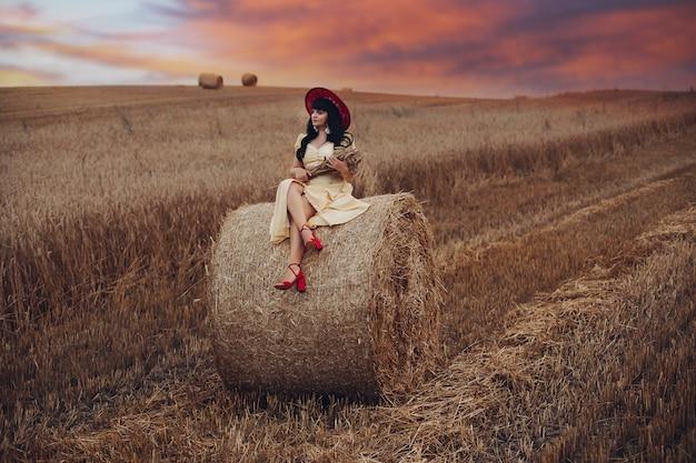 Vrij blanke vrouw met golvend lang zwart haar in lange gele jurk en rode hoed zit en ontspant