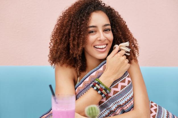 Vrij blij afro-amerikaanse vrouw recreëert in café, drinkt verse cocktail en omhelst kussen, in goed gezelschap van vrienden, geniet van vrije tijd.