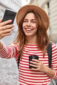 Vrij blije reiziger klikt op selfie-foto, maakt nieuwe foto's, gebruikt mobiele telefoon en applicatie