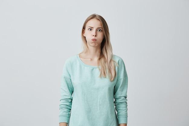 Vrij blond europees vrouwelijk model met ronde lippen, kijkt verbaasd, heeft een verbaasde uitdrukking, drukt haar emoties uit