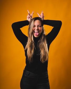 Vrij blond meisje dat haar handen over haar hoofd plaatst terwijl haar tong op een grappige en glimlachende manier uitsteekt, gekleed in een zwart shirt en broek