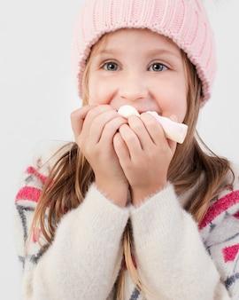 Vrij blond meisje dat snoepjes eet