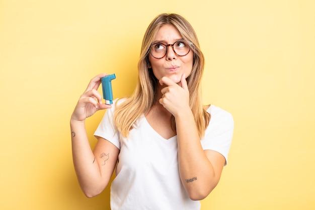 Vrij blond meisje denken, twijfelachtig en verward voelen. astma-inhalator concept
