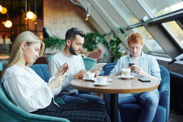 Vrij blond meisje en twee jongens zitten in blauwe zachte fluwelen fauteuils door tafel in café en met behulp van mobiele gadgets op uw gemak