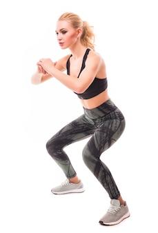 Vrij blond meisje in sportkleding werkt op haar lichaam