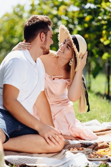 Vrij blond meisje in strohoed op romantische datum met knappe donkerbruine kerel