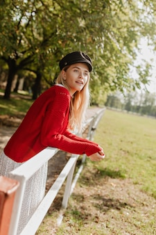 Vrij blond meisje met natuurlijke make-up poseren in de buurt van hek in het park. mooie vrouw die in aardige toebehoren verbaasd kijkt.