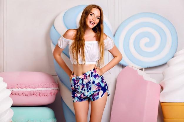 Vrij blond meisje met plezier in de buurt van gigantische zoetheid, lollies, ijs, bitterkoekjes, schattige trendy vrouwelijke outfit, lange haren, pastelkleuren, positieve sfeer.