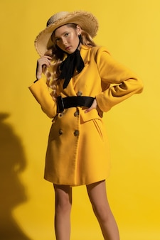 Vrij blond meisje met sproeten in gele outfit en strooien hoed op gele achtergrond