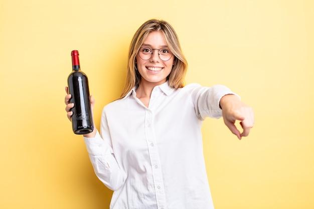 Vrij blond meisje wijzend op de camera die jou kiest. wijnfles concept