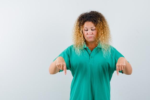 Vrij blonde dame die in groene polot-shirt naar beneden wijst en verdrietig kijkt. vooraanzicht.