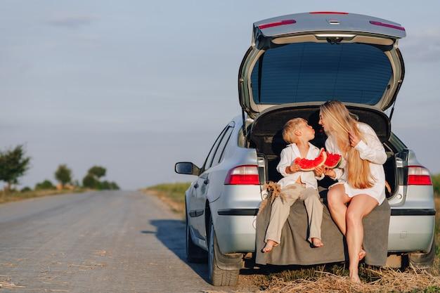 Vrij blonde haarvrouw met weinig blonde zoon bij zonsondergang die achter de auto ontspannen en watermeloen eten. zomer, reizen, natuur en frisse lucht op het platteland.
