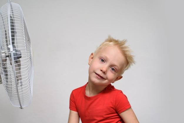 Vrij blonde jongen die in rood overhemd van de koele lucht geniet. zomer concept.
