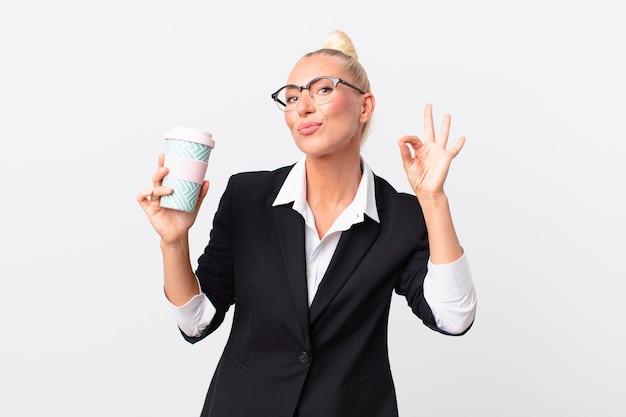 Vrij blonde volwassen zakenvrouw met een afhaalkoffie