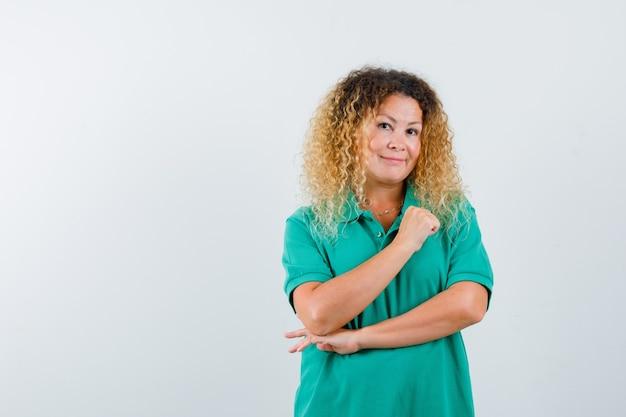 Vrij blonde vrouw die arm op de borst in groen polot-shirt houdt en vrolijk kijkt. vooraanzicht.