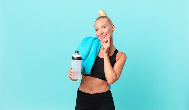 Vrij blonde vrouw die gelukkig glimlacht en dagdromen of twijfelt. fitnessconcept