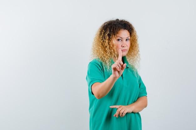 Vrij blonde vrouw die vasthouden aan een minuut gebaar in groen polot-shirt toont en ernstig, vooraanzicht kijkt.