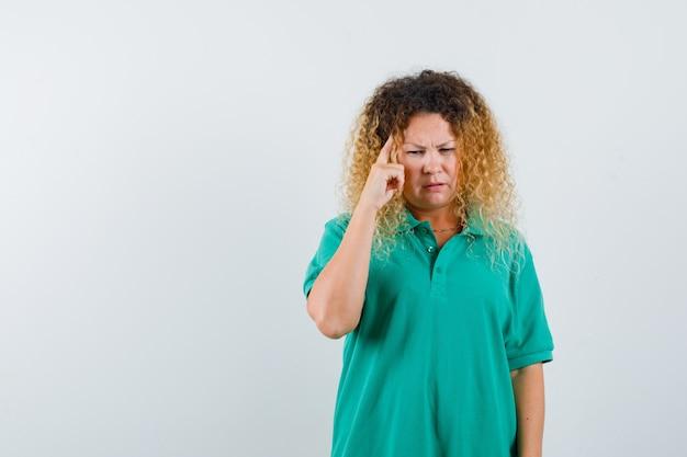 Vrij blonde vrouw die vinger op tempels in groen polot-shirt houdt en nadenkend kijkt. vooraanzicht.