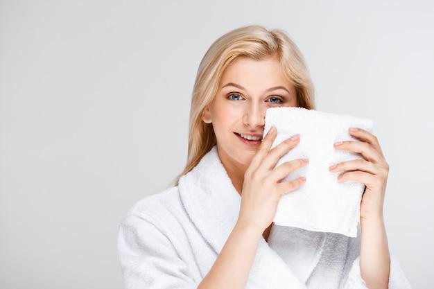 Vrij blonde vrouw in badjas met badhanddoek