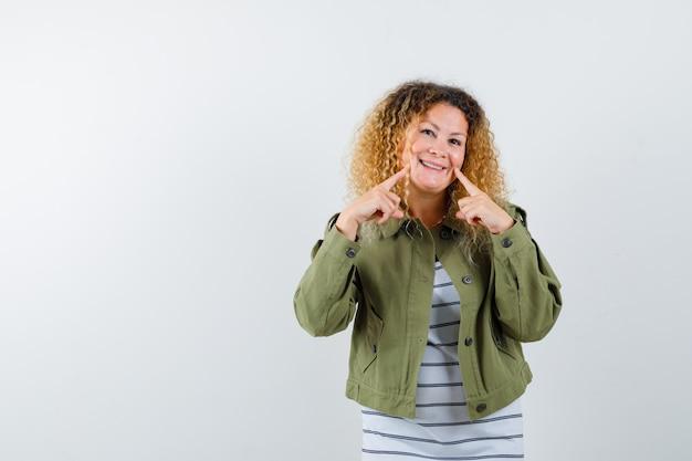 Vrij blonde vrouw in groen jasje wijzend op haar glimlach en op zoek vrolijk, vooraanzicht.