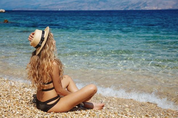 Vrij blonde vrouw in zwarte bikini en strohoed op strand