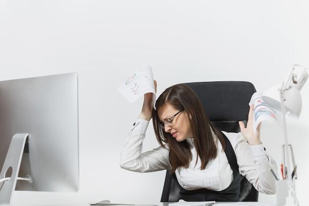 Vrij boze zakenvrouw in pak zittend aan de balie met documenten, werken op computer met moderne monitor in licht kantoor, vloeken en schreeuwen, problemen oplossen,
