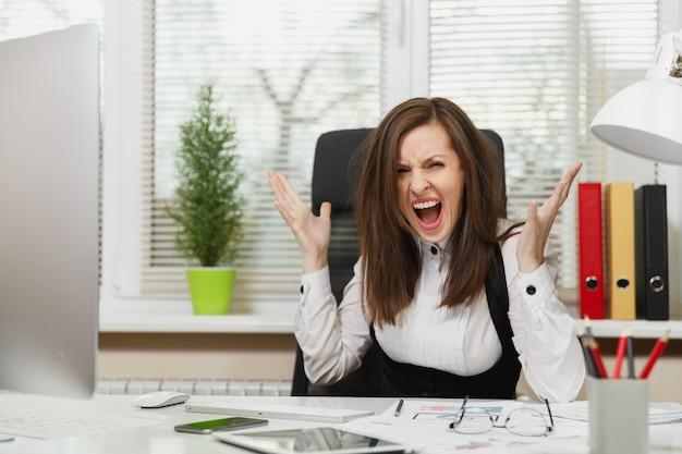 Vrij boze zakenvrouw in pak zittend aan de balie met tablet, werken op computer met moderne monitor met documenten in licht kantoor, vloeken en schreeuwen, problemen oplossen, emotie concept.