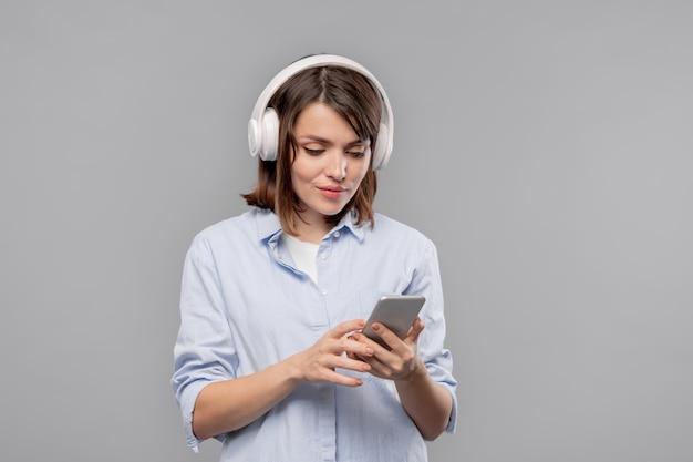 Vrij casual meisje met smartphone en koptelefoon scrollen door afspeellijst of video kijken