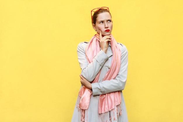 Vrij casual stijl meisje in jas en roze sjaal kreeg het idee en denken