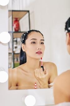 Vrij charmante jonge vrouw die lipgloss voor spiegel toepast tijdens het doen van make-up in de ochtend