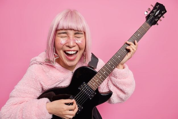 Vrij coole dolblije populaire zangeres speelt akoestische gitaar poses op concertpodium gekleed in bontjas