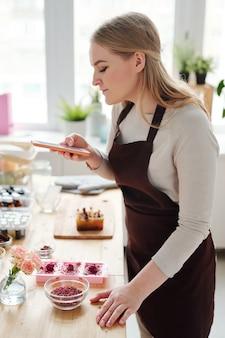 Vrij creatieve vrouw met smartphone die foto van handgemaakte zeep op tafel in de studio