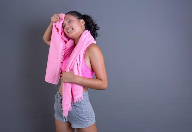 Vrij donkerbruin chinees meisje in sportkleding en zweet afvegen met handdoek op grijze achtergrond